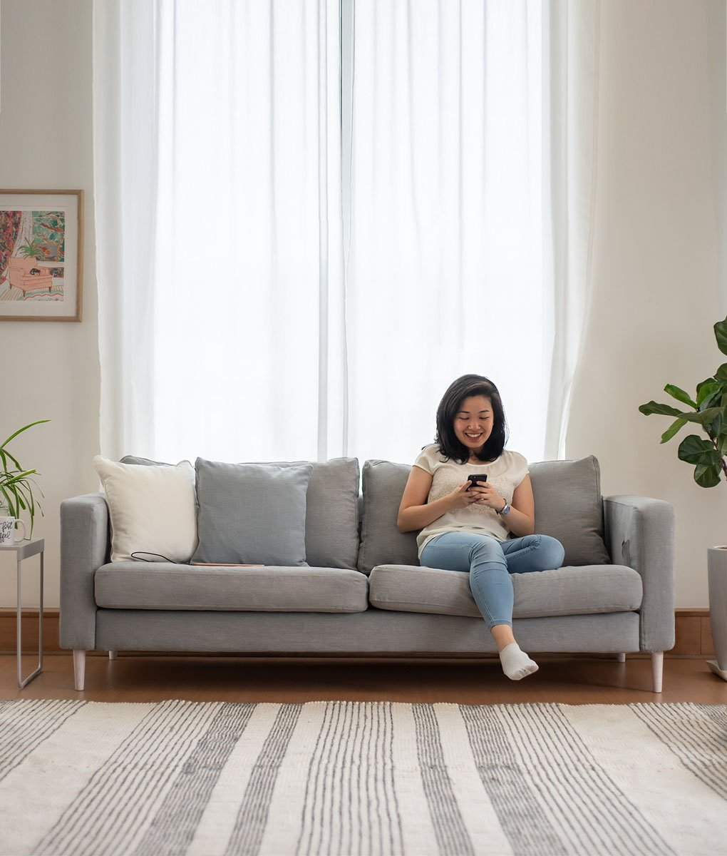 lady chilling and playing phone on ikea karlstad 3 seater sofa covered in madison ash panama cotton sofa cover slipcover